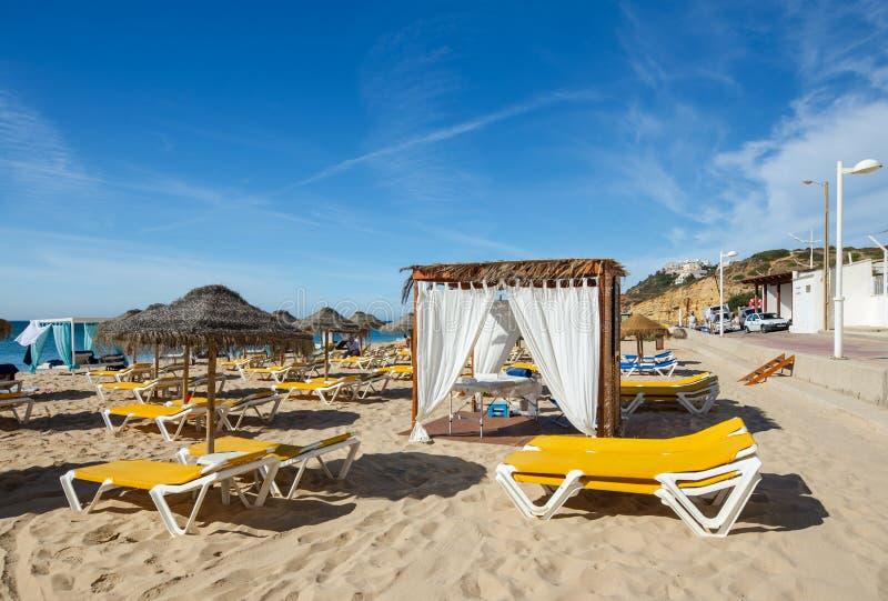 Las camas de Sun, los paraguas y el pabellón del masaje en el Salema varan, Algarve, Portugal meridional imagen de archivo