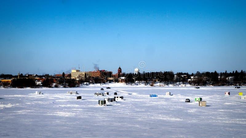 Las camionetas pickup conducen sobre el lago congelado con las casas de los pescados del invierno en fondo en Sunny Morning imagenes de archivo