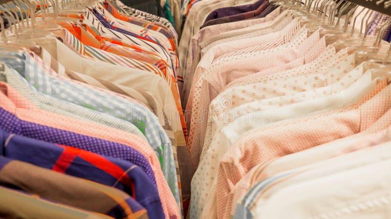 Las camisas de diversos colores cuelgan en tienda Camisas en suspensiones en tienda de la ropa foto de archivo
