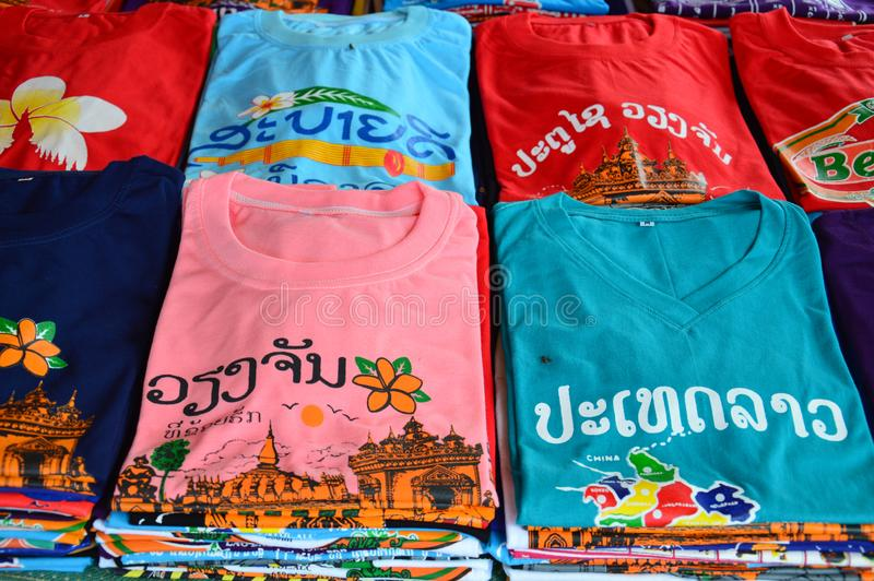 Las camisetas coloridas con las atracciones turísticas del Lao defienden la impresión vendida en la tienda de souvenirs en Vienti imagenes de archivo