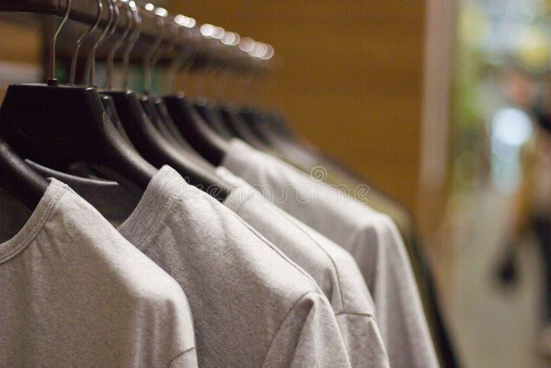 Las camisetas grises en suspensiones en la tienda de ropa, se cierran encima de la visión foto de archivo