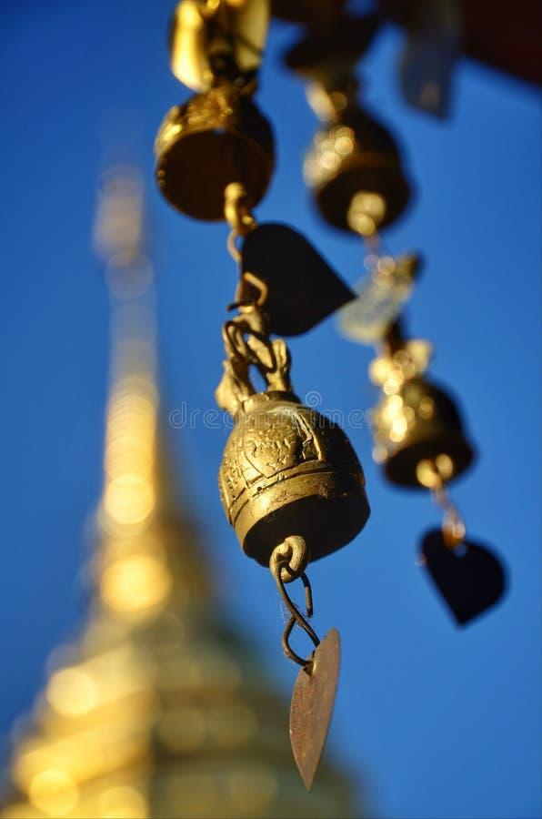 Las campanas de cobre amarillo cuelgan alrededor el pabellón en el área de templo imagenes de archivo