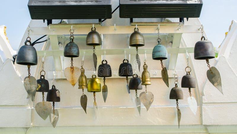 Las campanas de la ceremonia con la hoja de oro en el templo para hacen afortunado deseando en el soporte de oro un templo tailan foto de archivo libre de regalías