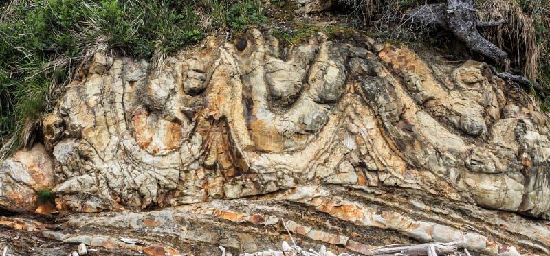 Las capas de roca forman el acantilado en la playa imágenes de archivo libres de regalías