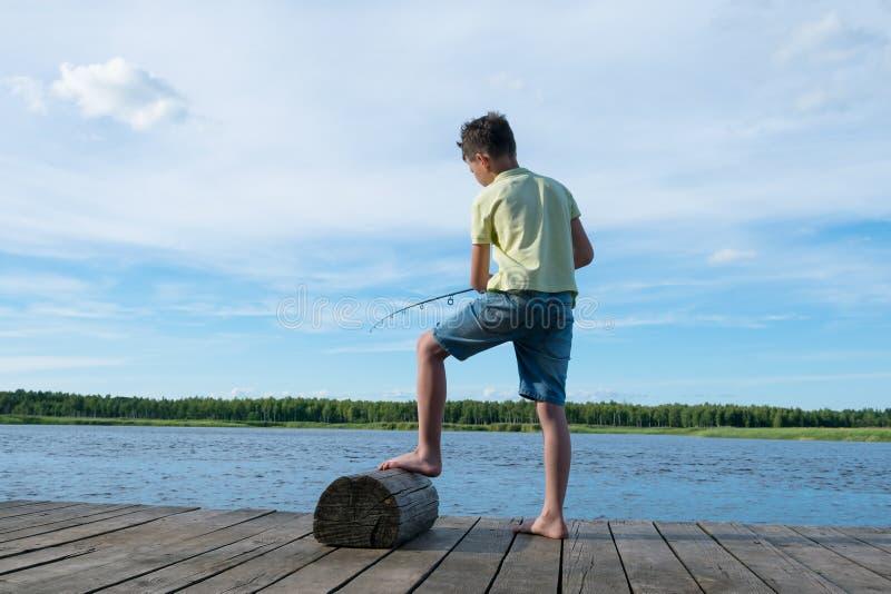 Las capturas del muchacho pescan con una caña de pescar en el lago contra el cielo hermoso, vista posterior fotos de archivo