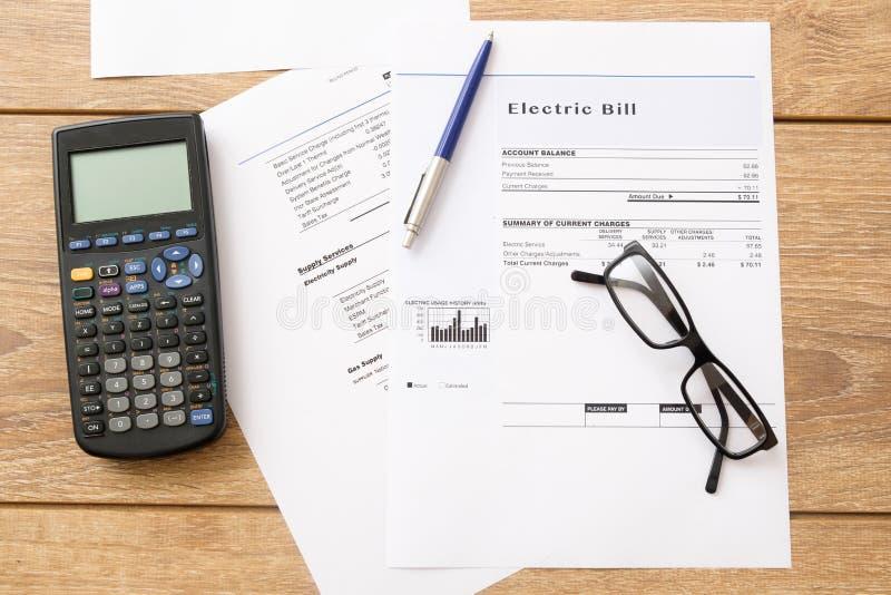 Las cargas de cuenta de la electricidad empapelan la forma en una tabla fotos de archivo libres de regalías