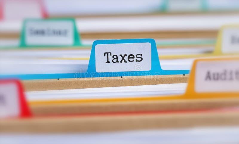 Las carpetas de archivos con una etiqueta etiquetaron impuestos foto de archivo libre de regalías