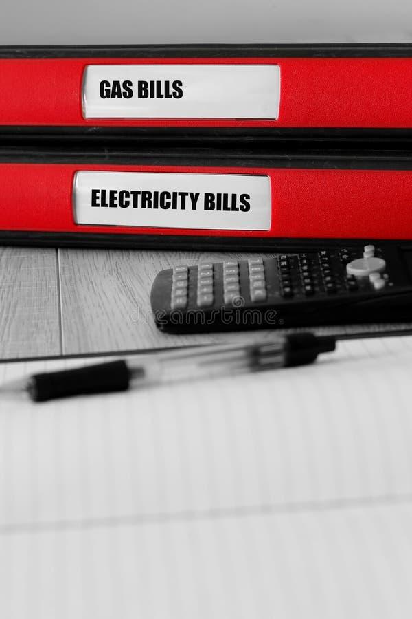 Las carpetas rojas con el gas y la electricidad cargan en cuenta escrito en la etiqueta en un escritorio foto de archivo libre de regalías
