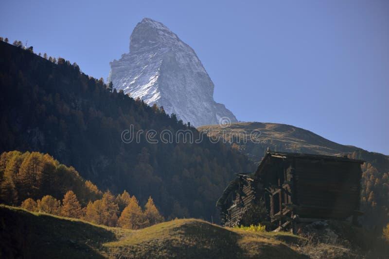Las casas antiguas de madera del pueblo viejo de Zermatt con Cervino enarbolan en fondo foto de archivo libre de regalías