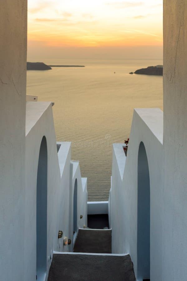 Las casas blancas y la puesta del sol ajardinan en la ciudad del imerovigli, isla de Santorini, Thira, Grecia fotografía de archivo