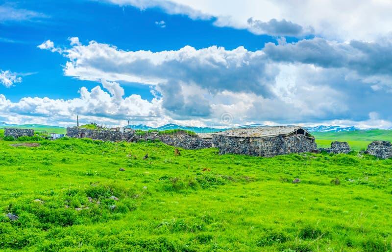 Las casas de piedra viejas en un prado imagen de archivo libre de regalías
