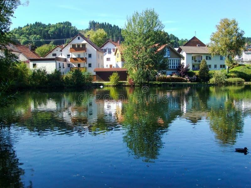 Las casas pusieron contra una charca en Peiting, Alemania foto de archivo