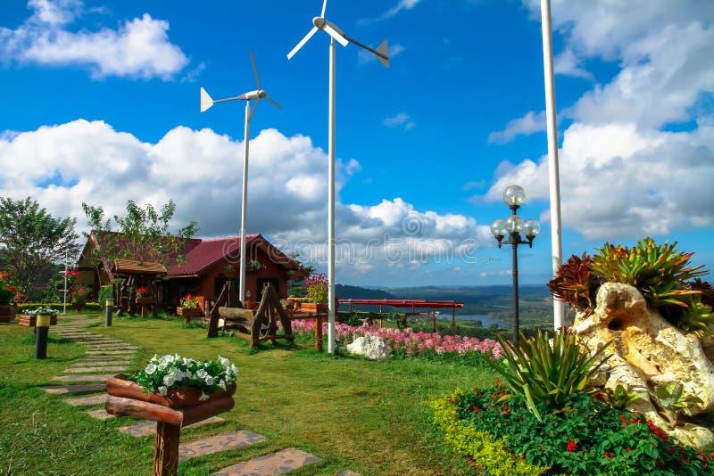 Las casas tienen un jardín de flores con turbinas de viento y un bl hermoso imágenes de archivo libres de regalías