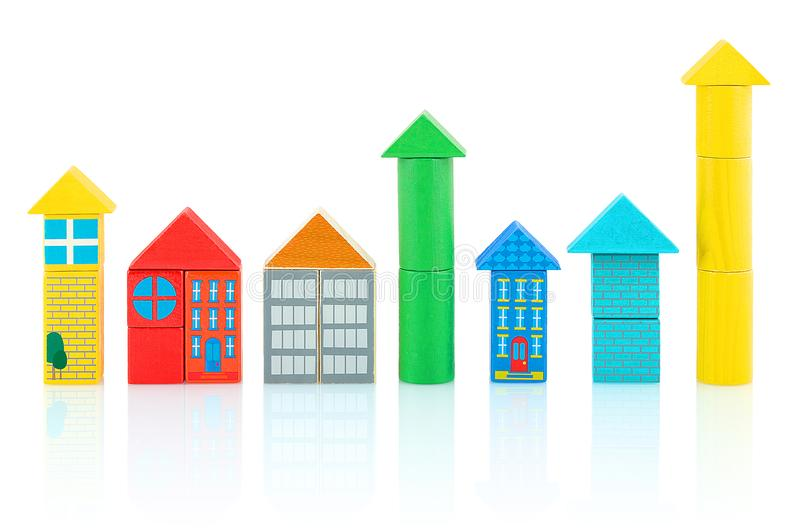 Las casas y las torres builded de los bloques de madera coloridos aislados en el fondo blanco con la reflexión de la sombra foto de archivo libre de regalías