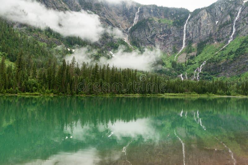 Las cascadas reflejan en el lago verde imagenes de archivo