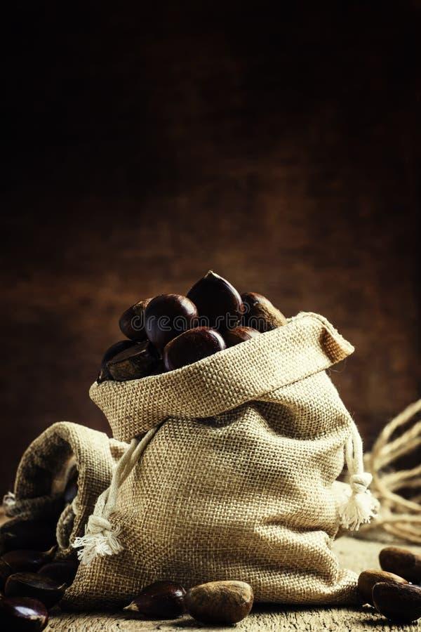Las castañas comestibles frescas en una lona empaquetan en backgro de madera del vintage fotos de archivo libres de regalías