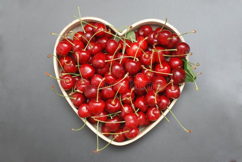 Las cerezas frescas dan fruto con las hojas en la caja de madera de la forma del corazón, visión superior Bayas del rojo del vera imágenes de archivo libres de regalías