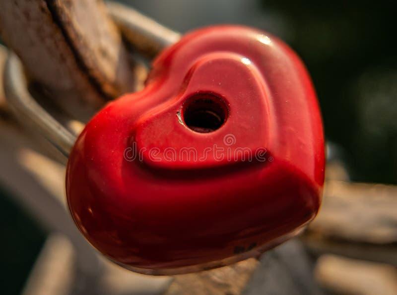 Las cerraduras rojas pesan en la verja foto de archivo