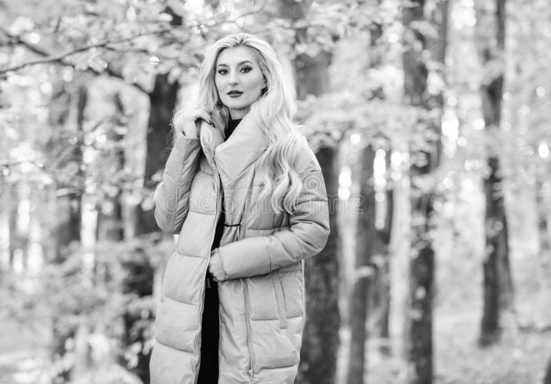 Las chaquetas todo el mundo deben tener Paseo rubio de moda de la muchacha en parque Las mejores capas del fumador a comprar C?mo imágenes de archivo libres de regalías