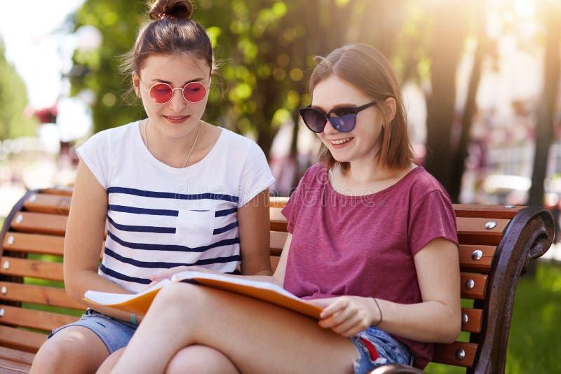 Las chicas jóvenes alegres pasan el tiempo junto en día soleado caliente en el parque Las bellezas miran a través de la revista d imagenes de archivo