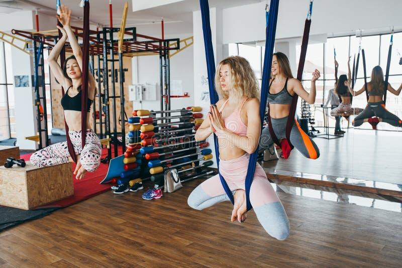 Las chicas jóvenes hacen yoga aérea en el gimnasio fotos de archivo libres de regalías