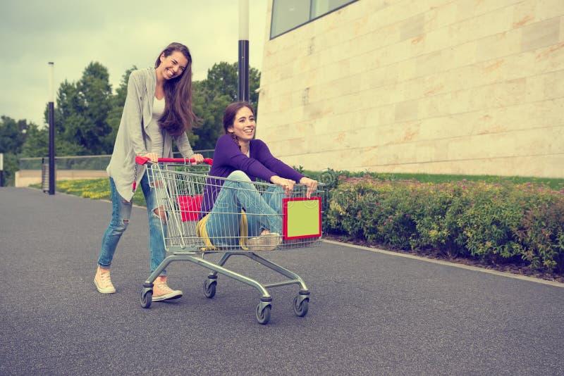 Las chicas jóvenes se divierten con la carretilla de las compras imágenes de archivo libres de regalías