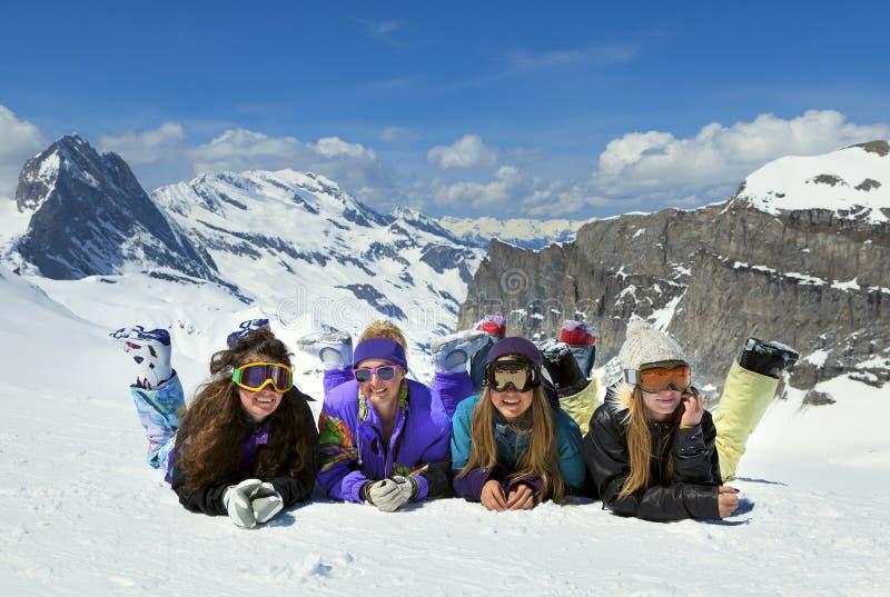 Las chicas jóvenes son snowboarders en montañas imagen de archivo libre de regalías