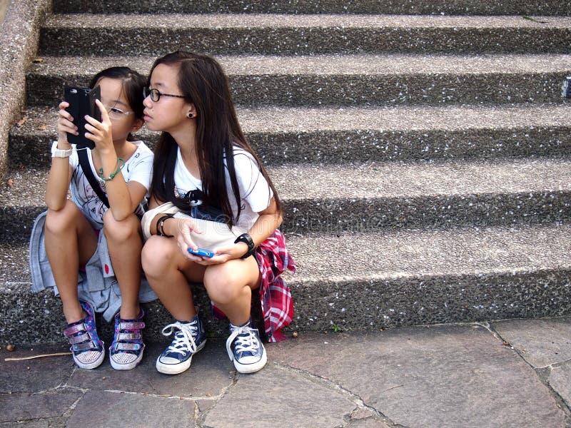 Las chicas jóvenes utilizan su teléfono móvil o smartphone mientras que se sientan en una escalera en Tampines, Singapur fotos de archivo libres de regalías