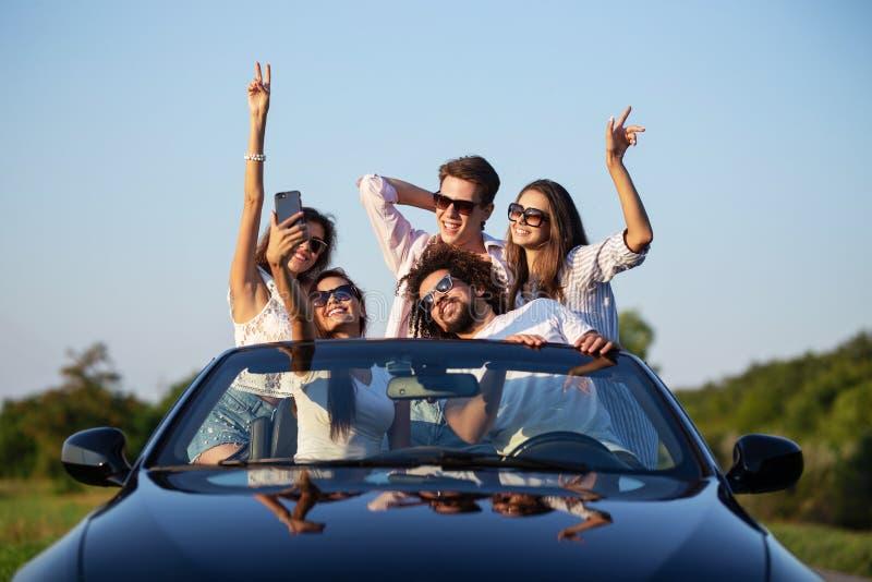 Las chicas jóvenes y los individuos alegres en gafas de sol se están sentando en un coche convertible negro en el camino que leva imagenes de archivo