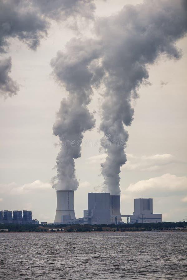 Las chimeneas múltiples de la central eléctrica del combustible fósil del carbón emiten el carbono foto de archivo libre de regalías