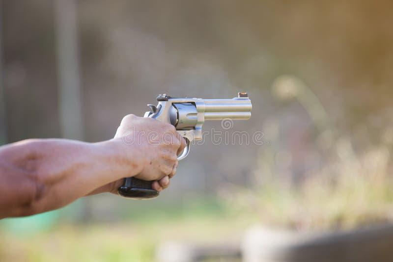 Las chispas del arma, balas tiraron fuera del barril y del humo imagenes de archivo