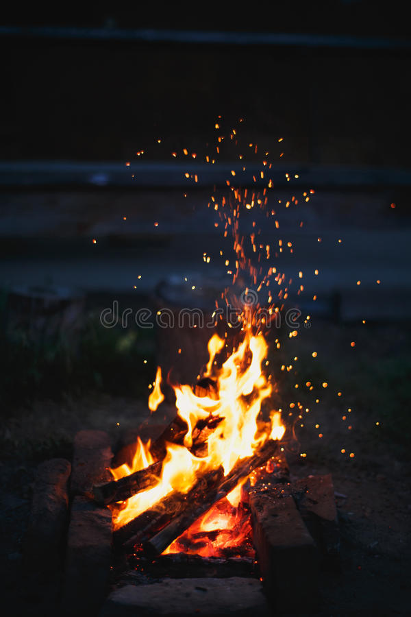 Las chispas vuelan del fuego imagenes de archivo