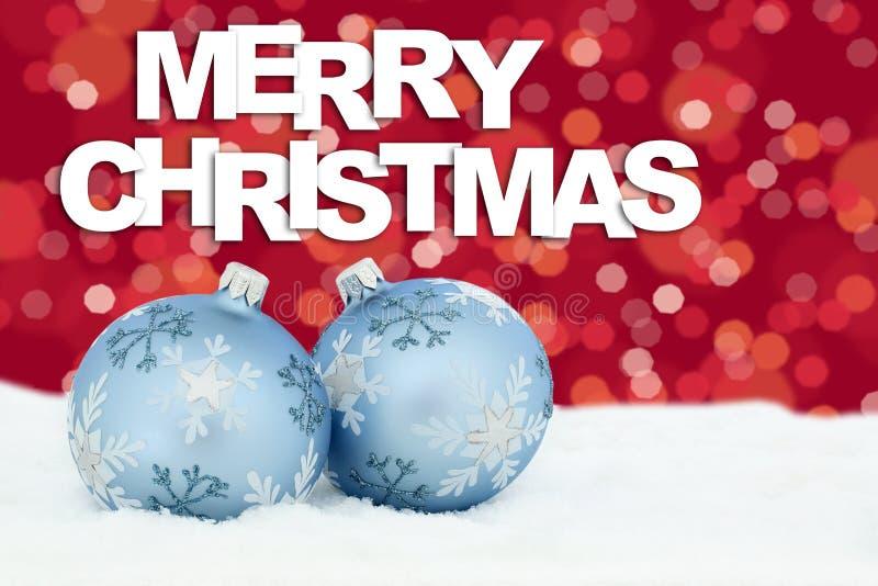 Las chucherías de las bolas de la tarjeta de la Feliz Navidad protagonizan el decorat de la nieve del fondo fotos de archivo libres de regalías