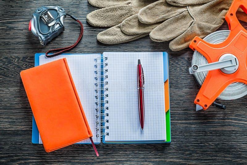 Las cintas métricas rodadas cubren la pluma de los cuadernos con cuero de los guantes protectores encendido foto de archivo