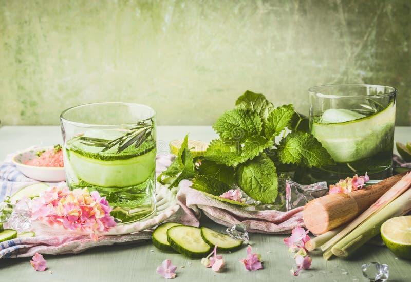 Las clases con limonada o el detox del pepino infundieron los cubos del agua y de hielo en la tabla con los ingredientes Restaura imágenes de archivo libres de regalías
