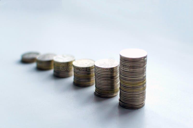 Las columnas cada vez mayores de las monedas, miradas tienen gusto como carta de crecimiento, paso de la moneda de las pilas aisl fotos de archivo