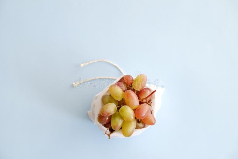 Las composiciones de Minimalistic con el manojo de uvas rellenas en algodón reciclable de la tela empaquetan foto de archivo libre de regalías