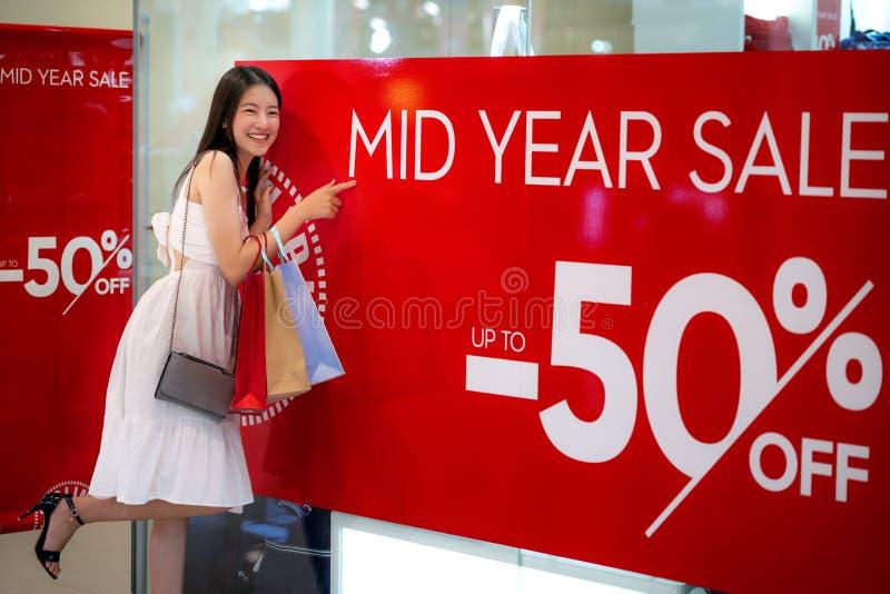 Las compras asiáticas de la muchacha con la mediados de venta 50 del año percen de la promoción foto de archivo