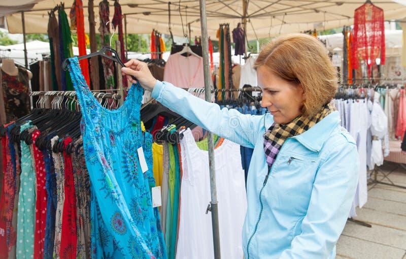 Las compras de la mujer joven se visten en mercado imagenes de archivo