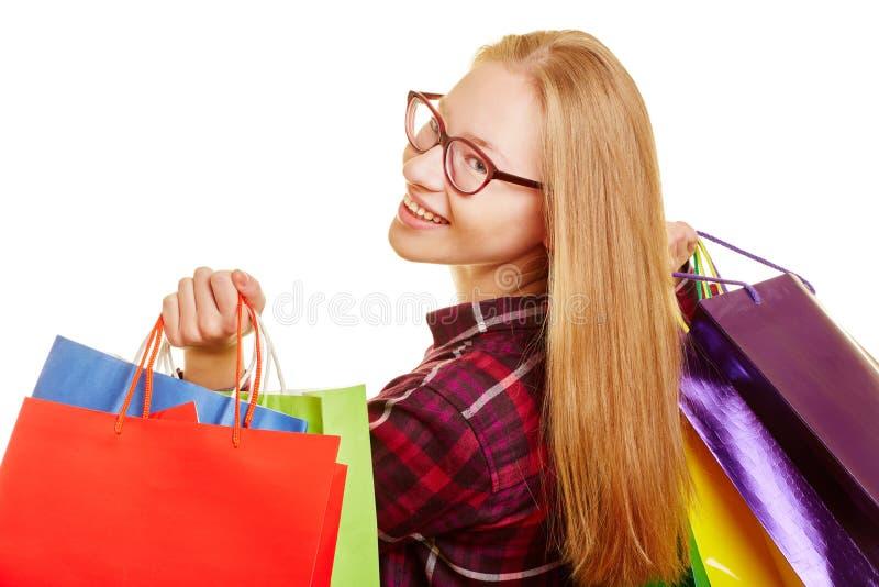 Las compras de la mujer miran sobre su hombro fotos de archivo