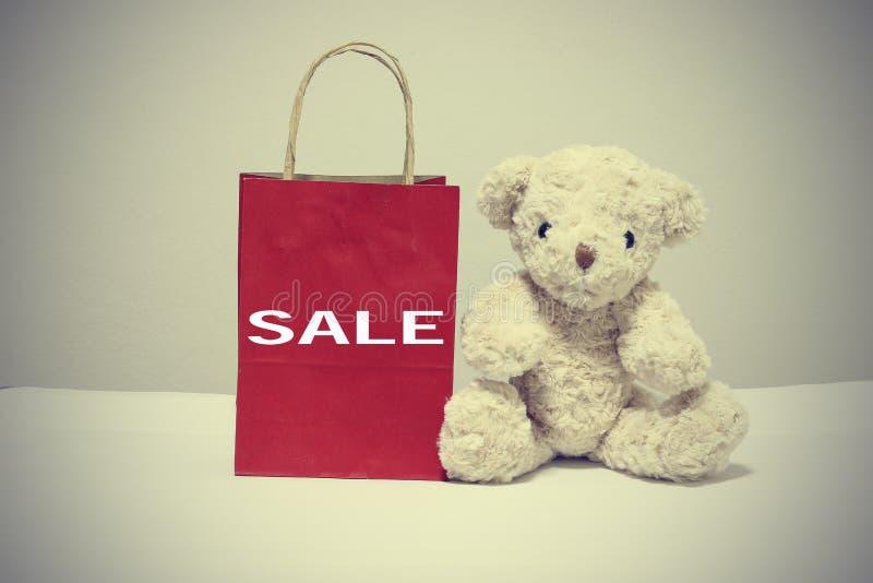 Las compras del oso de peluche y de la bolsa de papel mecanografían la venta de la palabra Estilo de la vendimia foto de archivo