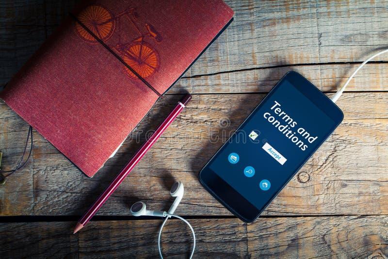Las condiciones documentan en una pantalla del teléfono móvil Concepto legal foto de archivo libre de regalías