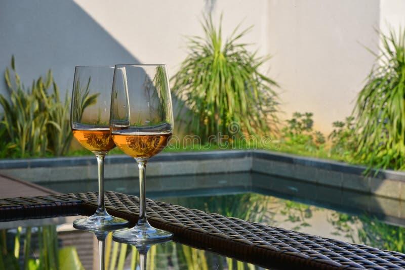 Las copas de vino en la tabla por la piscina imagen de archivo libre de regalías