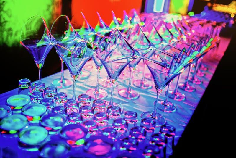 Las copas de vino vacías coloridas coinciden en el contador de la barra en el partido del club nocturno imagenes de archivo