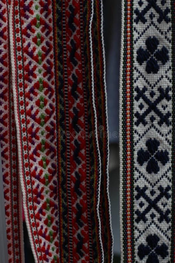 Las correas letonas tradicionales son correas se hacen con el hilado, artefactos preciosos, variedad de colores, diferente en reg imagenes de archivo