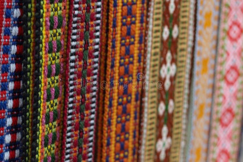 Las correas letonas tradicionales son correas se hacen con el hilado, artefactos preciosos, variedad de colores, diferente en reg fotografía de archivo