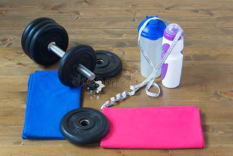 Las cosas para el deporte mienten suavemente en el piso y la pesa de gimnasia plegable imagen de archivo libre de regalías