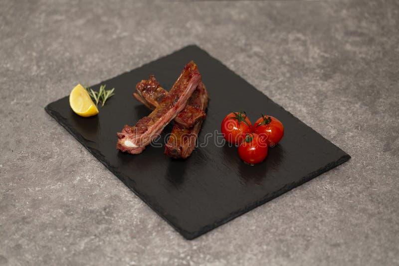 Las costillas de cerdo en salsa y miel de barbacoa asaron los tomates en un plato negro de la pizarra fotografía de archivo