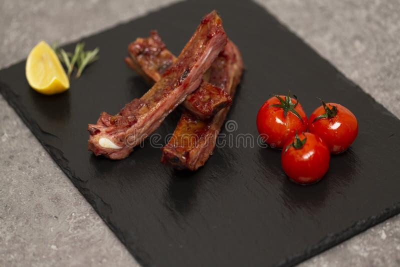 Las costillas de cerdo en salsa y miel de barbacoa asaron los tomates en un plato negro de la pizarra fotos de archivo