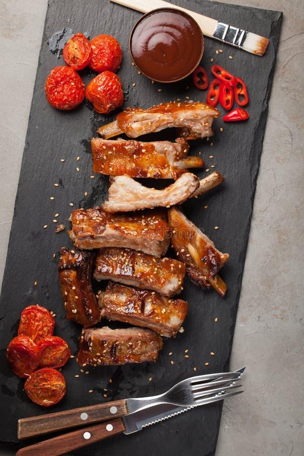 Las costillas de cerdo en salsa y miel de barbacoa asaron los tomates en un plato negro de la pizarra Un gran bocado a la cerveza fotografía de archivo